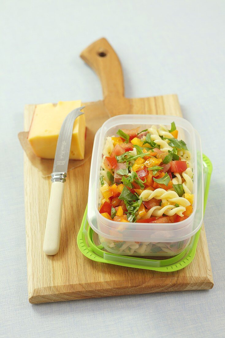 Pasta salad with tomato and pepper in a plastic box