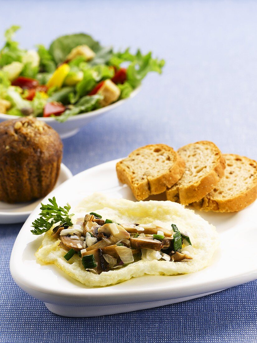 An egg-white omelette with mushrooms and bread with a muffin and a side salad in the background