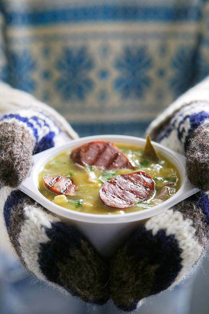 A pair of hands in woollen mittens holding a bowl of pea soup with sausage