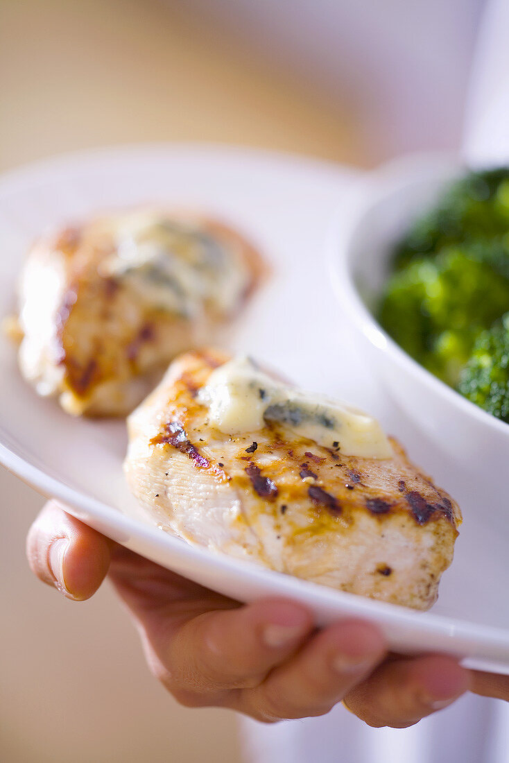Man carrying grilled chicken breast with Gorgonzola sauce