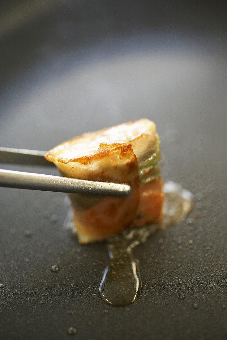 Halibut wrapped in mint and ham, held in tweezers