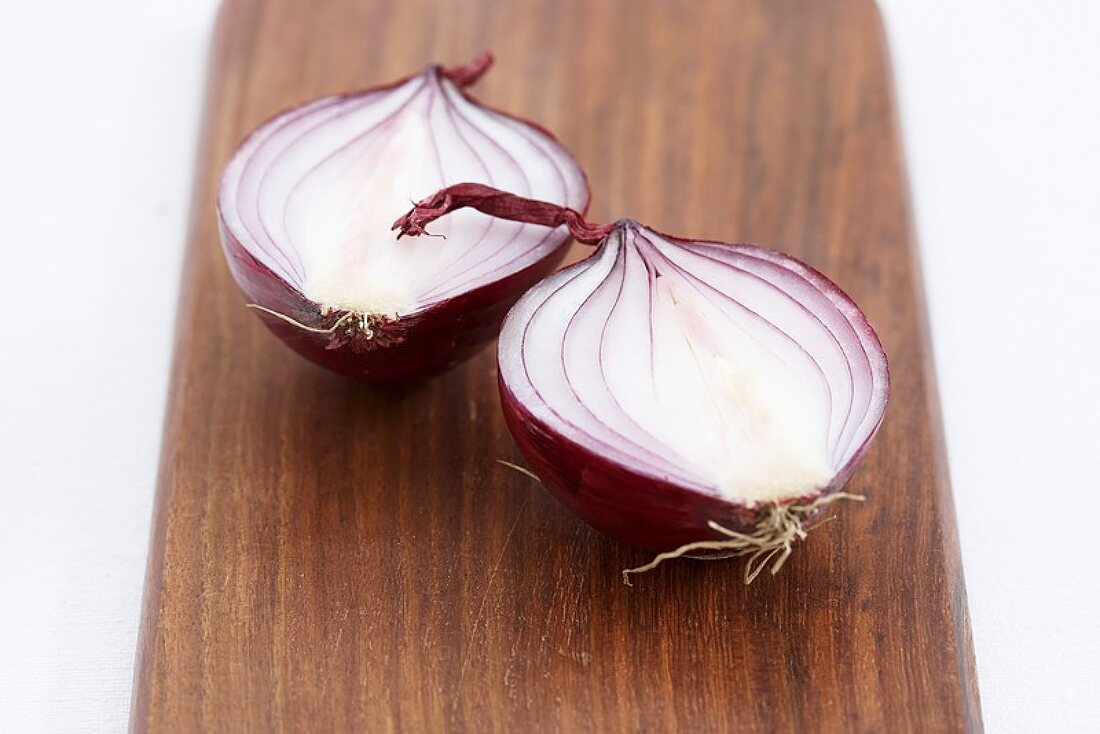 A halved red onion on a wooden background