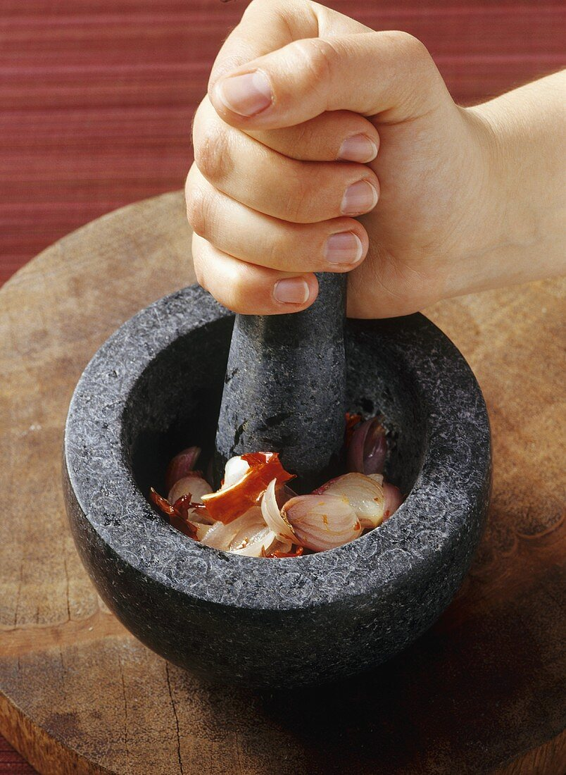 Crushing ingredients for curry paste in a stone mortar