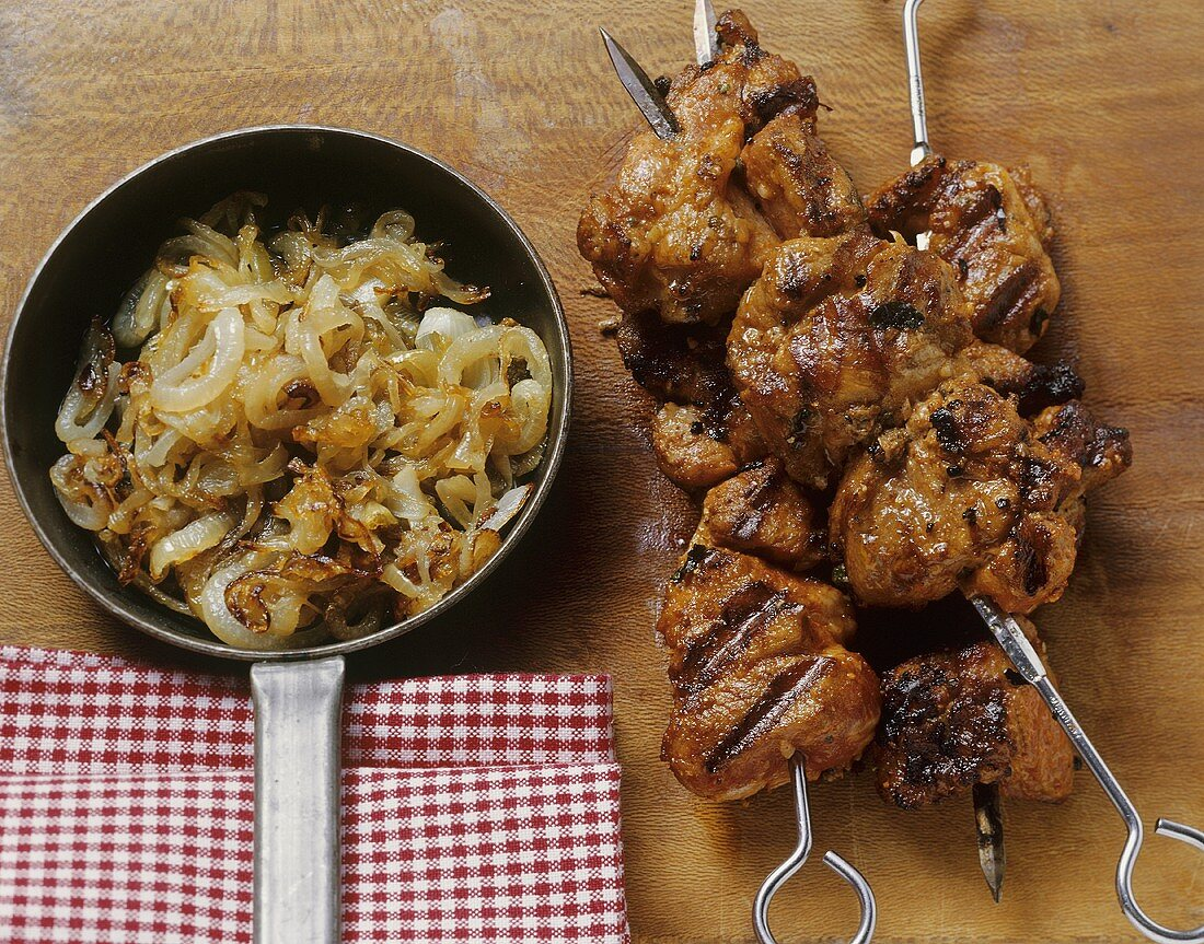 Grilled pork kebabs with fried onions