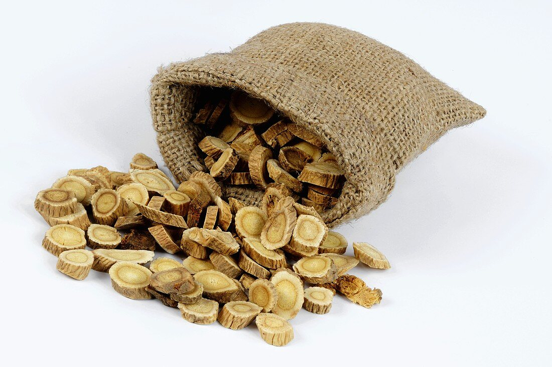 Slices of astragalus root spilling out of a jute sack