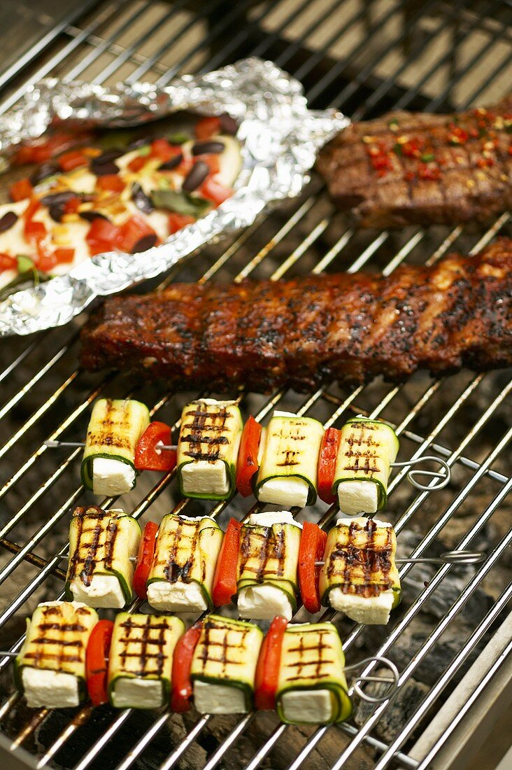 Pork ribs, courgette kebabs, charr, steak on barbecue