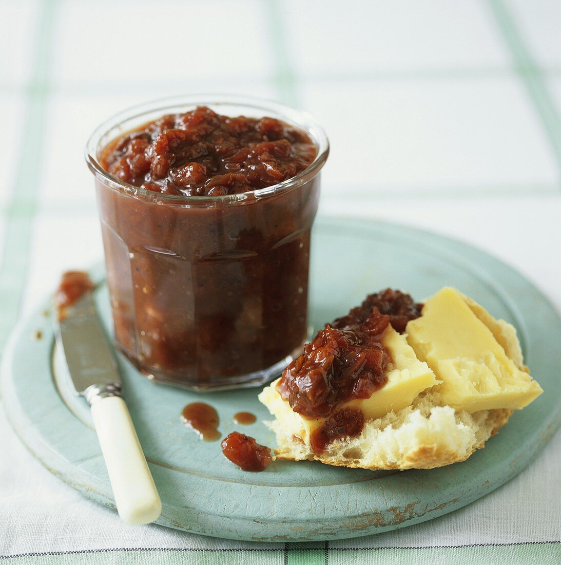 Plum chutney in a jar and on a piece of bread and cheese