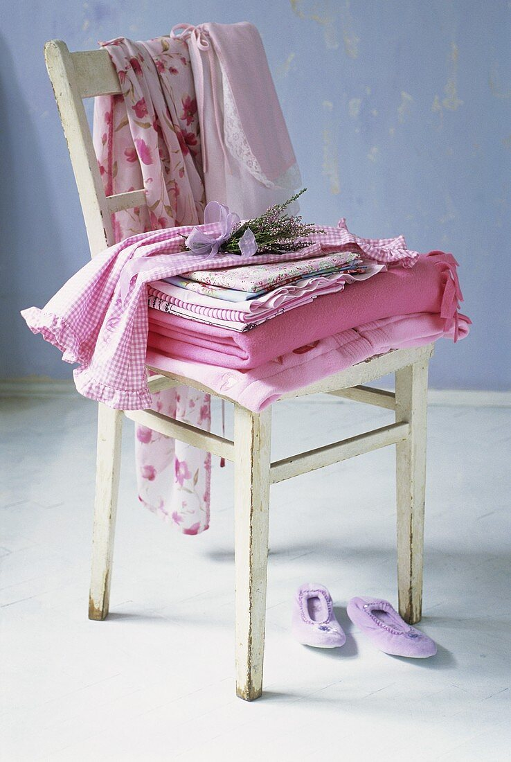 Bedding and clothes on wooden chair