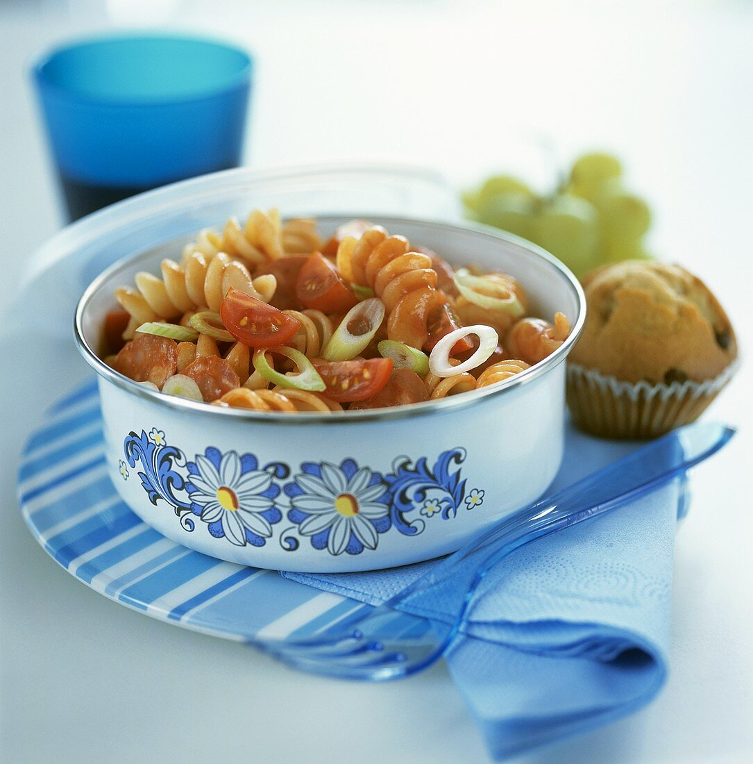 Pasta salad with sausage, tomatoes, spring onions, tomato sauce