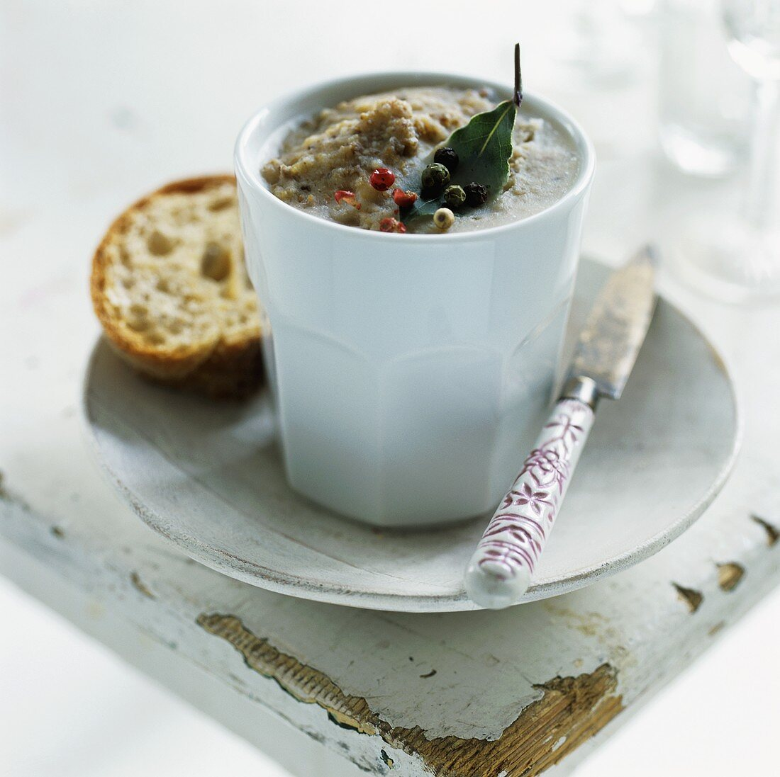 A beaker of pork dripping with knife and bread