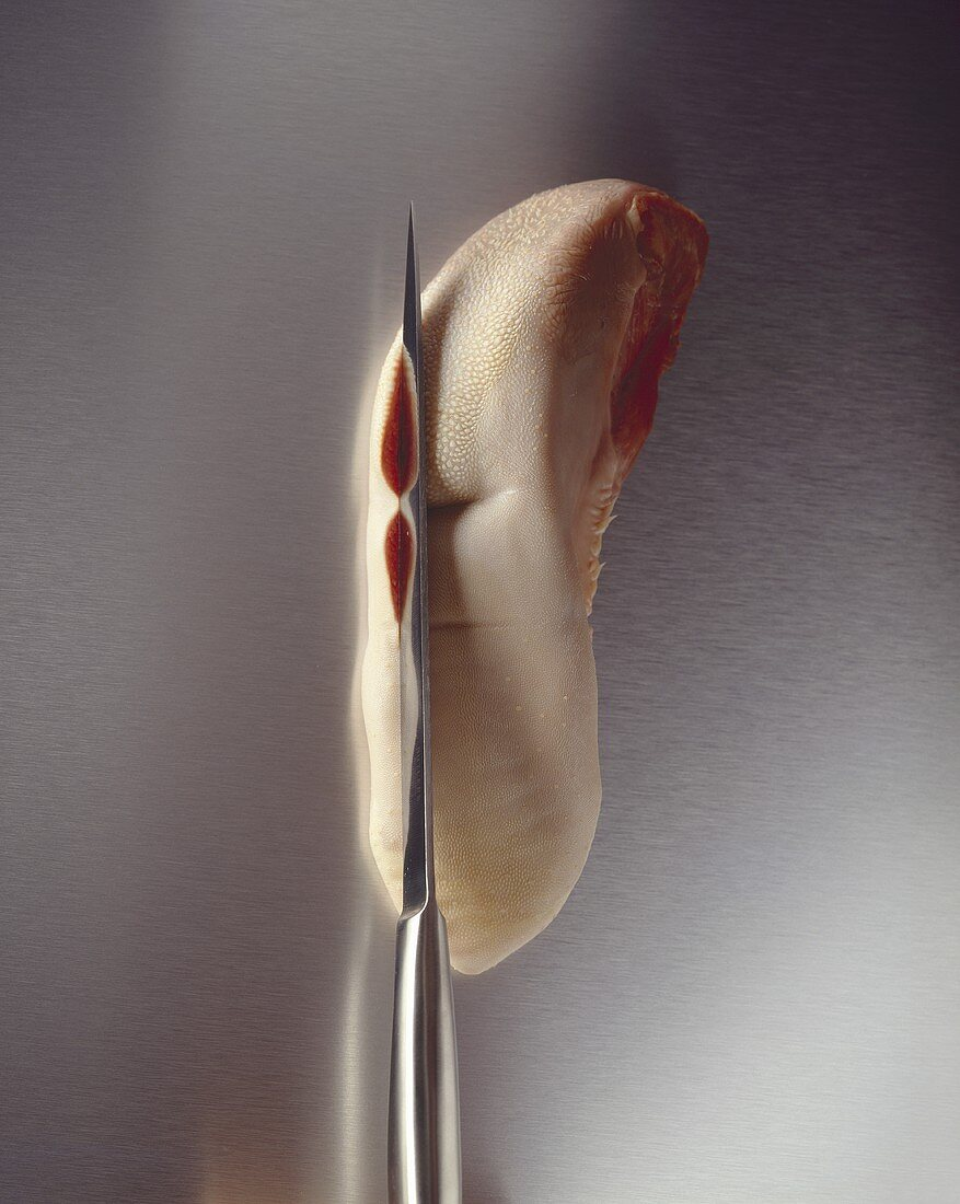Skinning a veal tongue with a knife