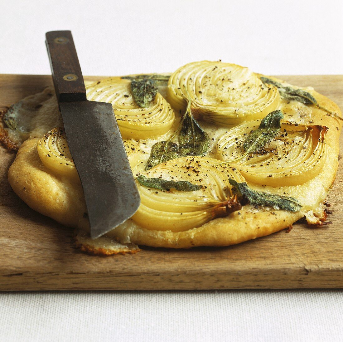 Onion and sage pizza with knife on chopping board