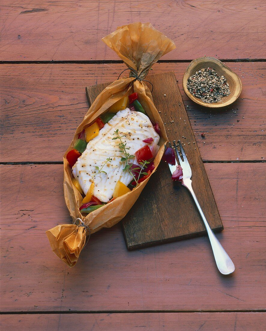 Cod with peppers in parchment paper, mixed pepper