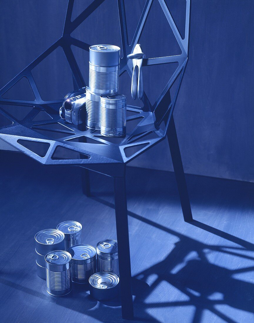 Assorted food tins on and under an iron chair