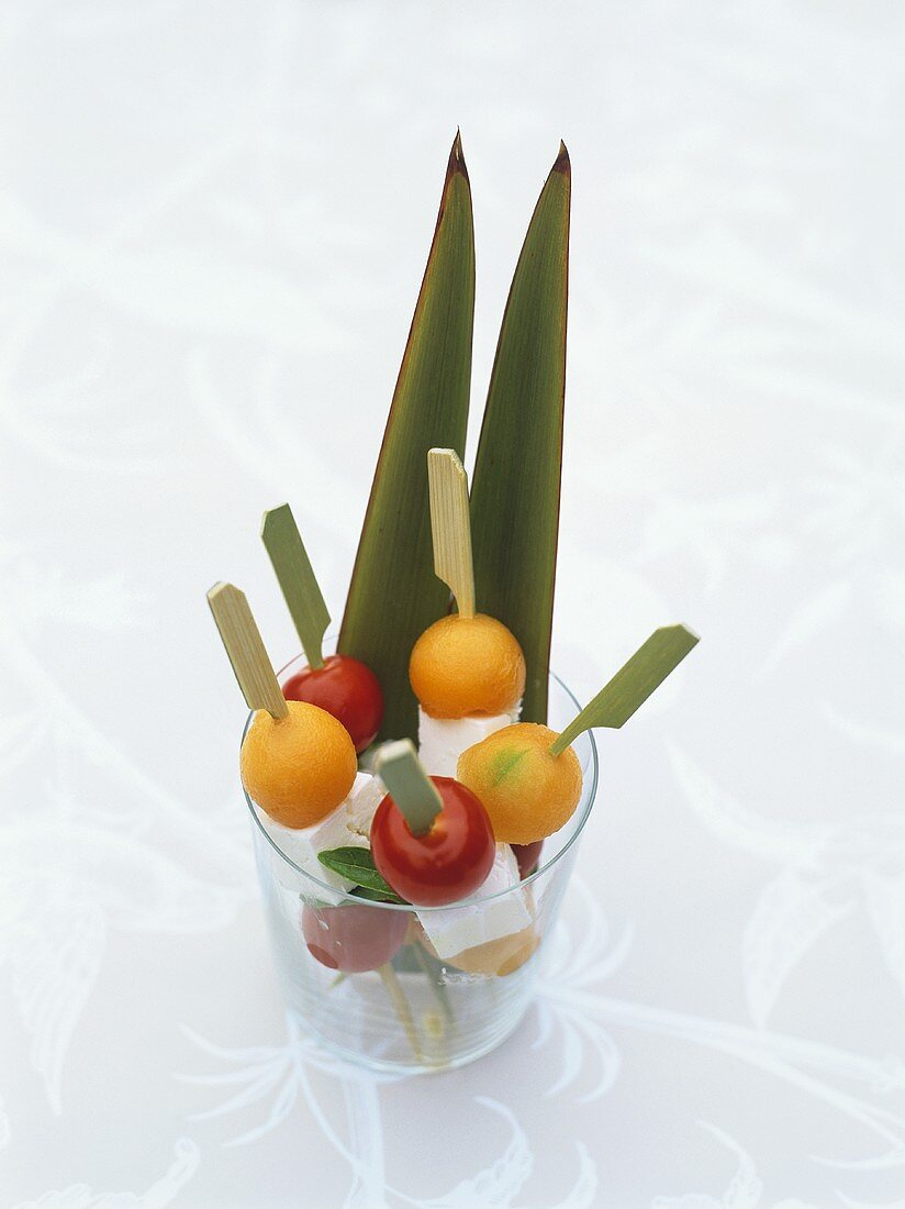Tomatoes and feta on cocktail sticks in a glass