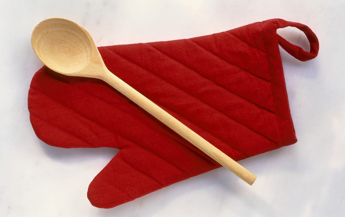 Wooden spoon on a red oven glove