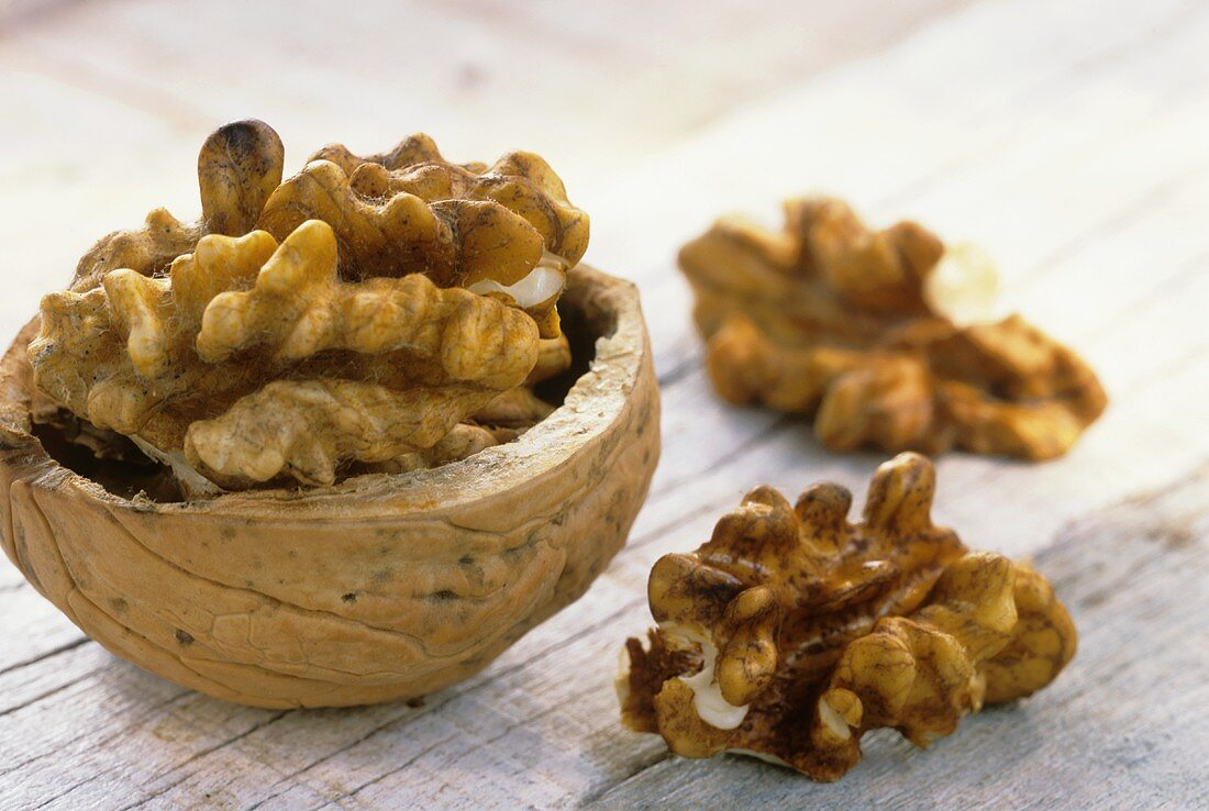 Walnut in half shell and two shelled walnuts on wooden background