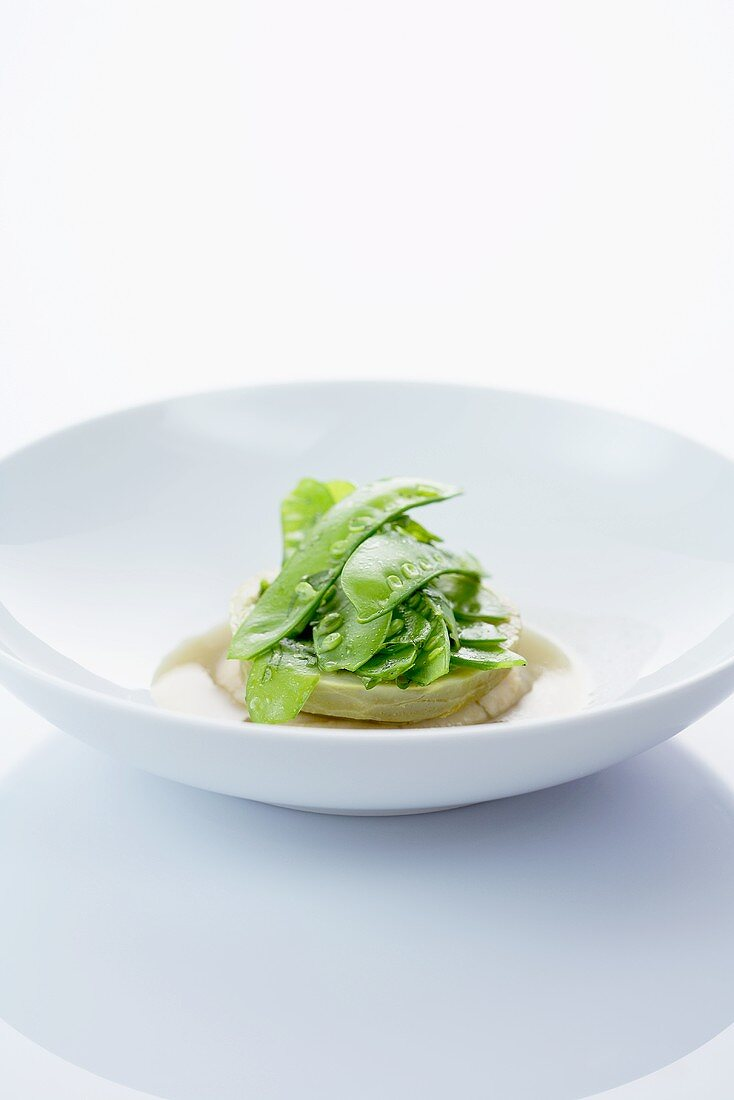 Artichoke in broth with bean cream and a mange tout salad