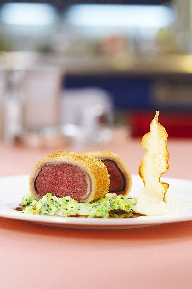 Saddle of venison wrapped in bread with cream savoy cabbage and celery chips