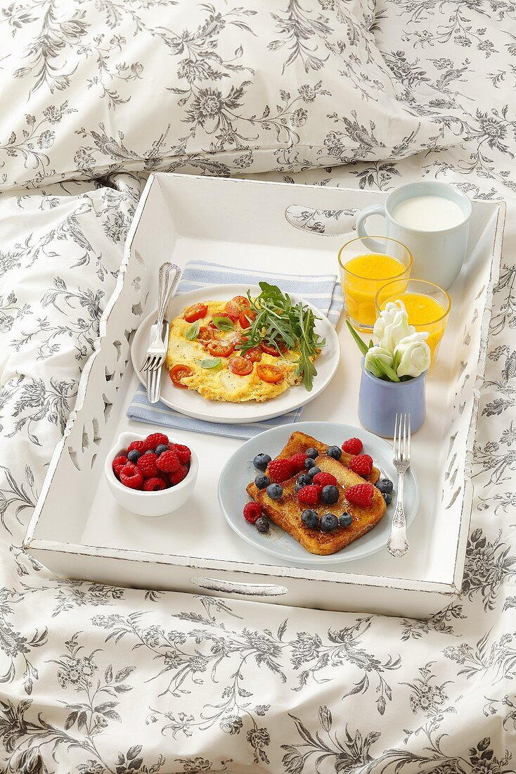 Breakfast in bed (French toast, omelette with cherry tomatoes, orange juice and milk)