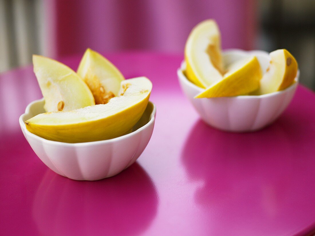 Melon slices in white bowls on a pink surface