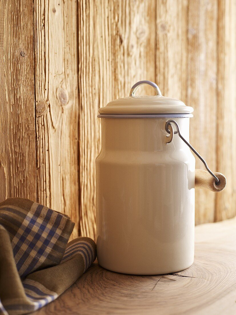 A milk churn in front of a wooden wall
