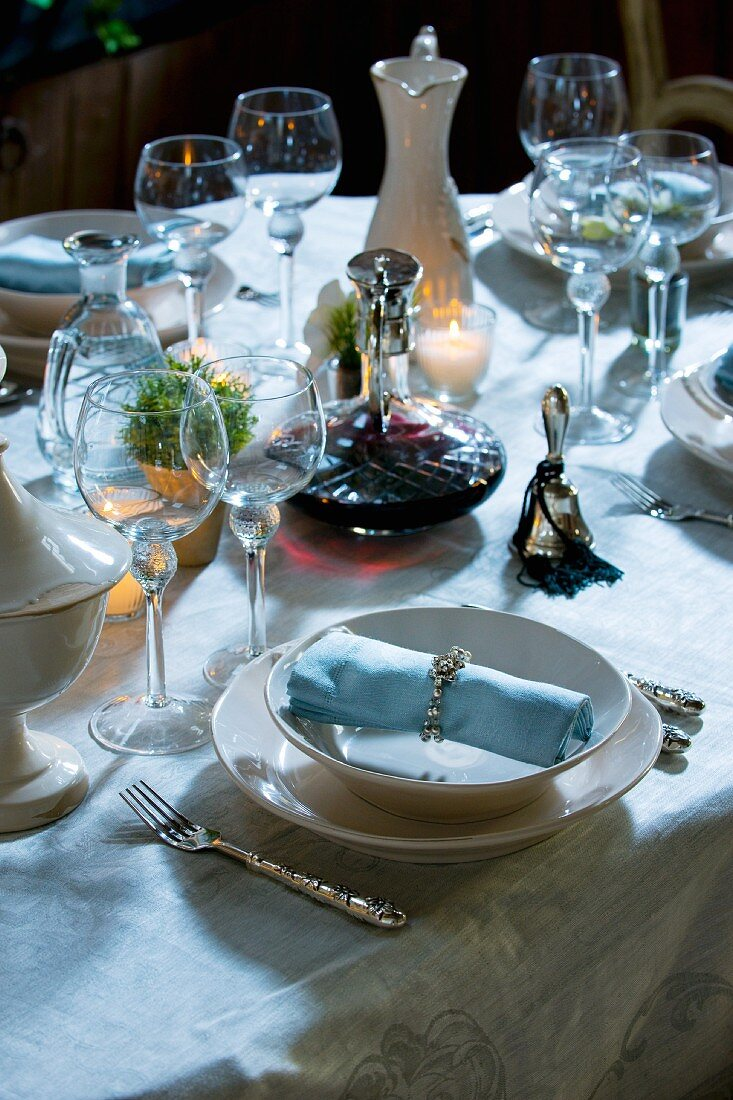 Table laid for special occasion with carafe of wine, bell & candles