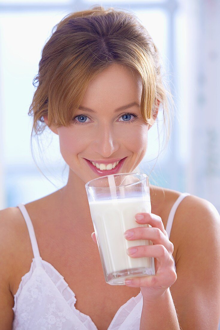 Young woman drinking a glass of milk