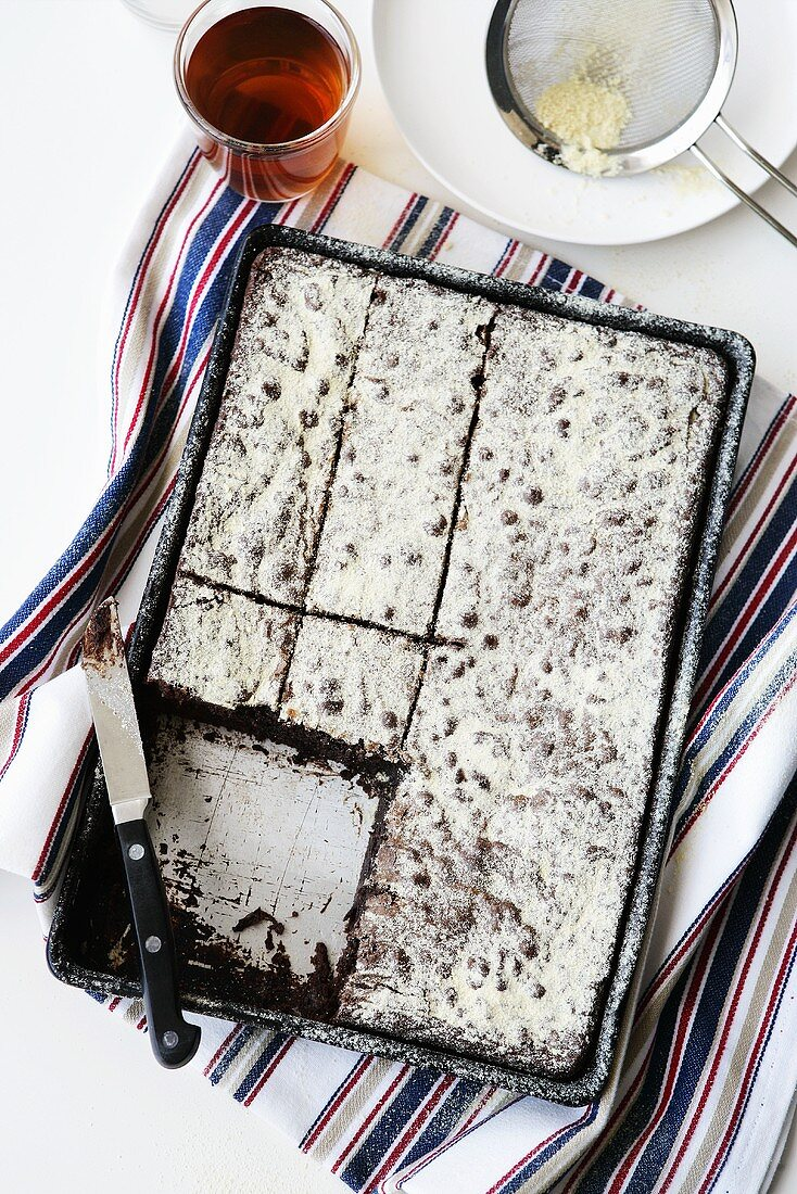 Chocolate malt brownies with icing sugar in baking tin