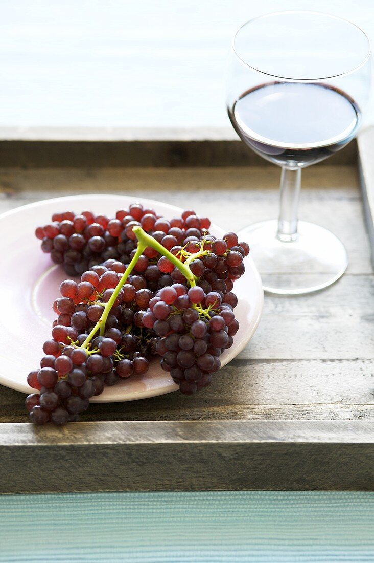 Red grapes and a glass of red wine on a tray