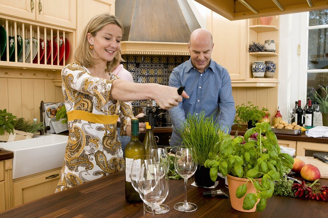 Couple in kitchen, surrounded by fresh herbs