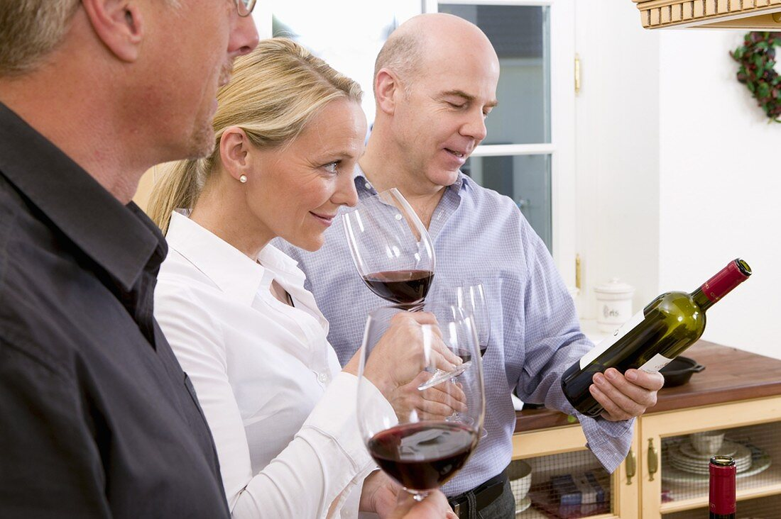 A woman and two men tasting red wine