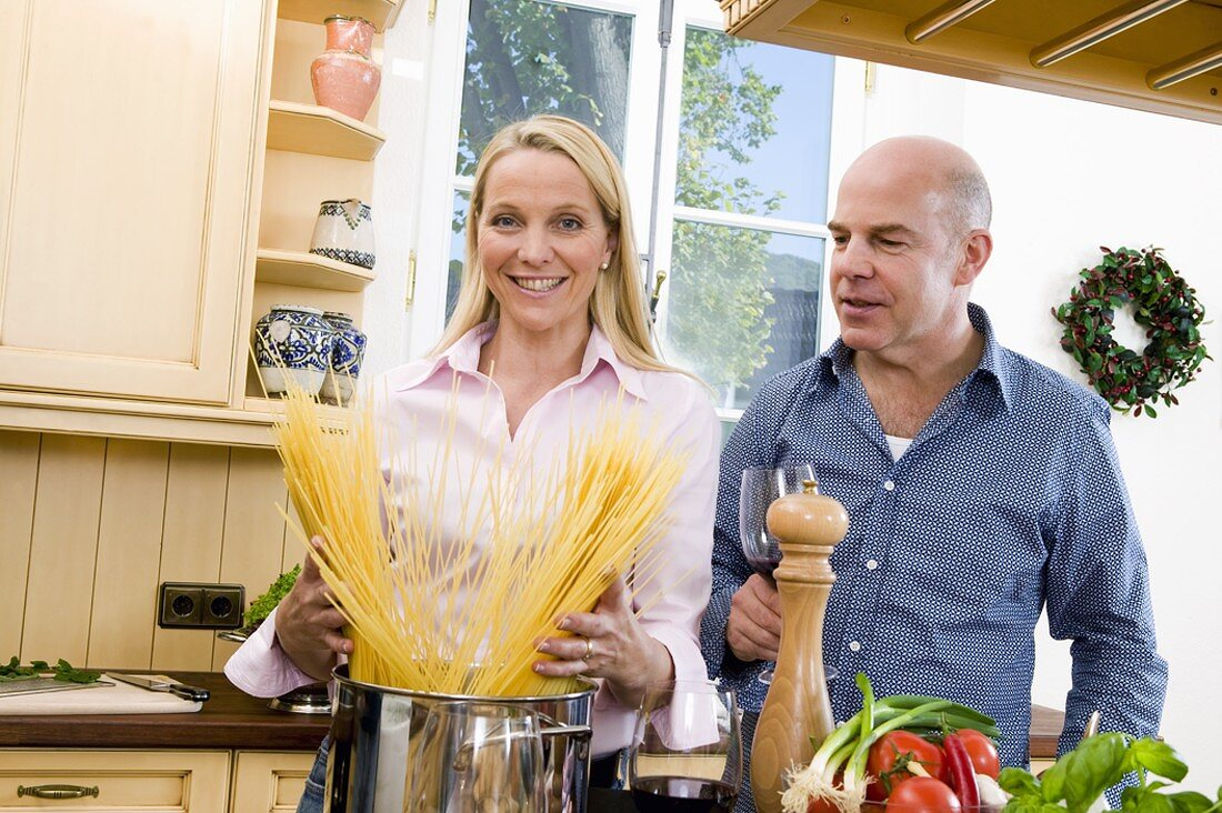 Woman putting spaghetti into pan, man beside her with red wine