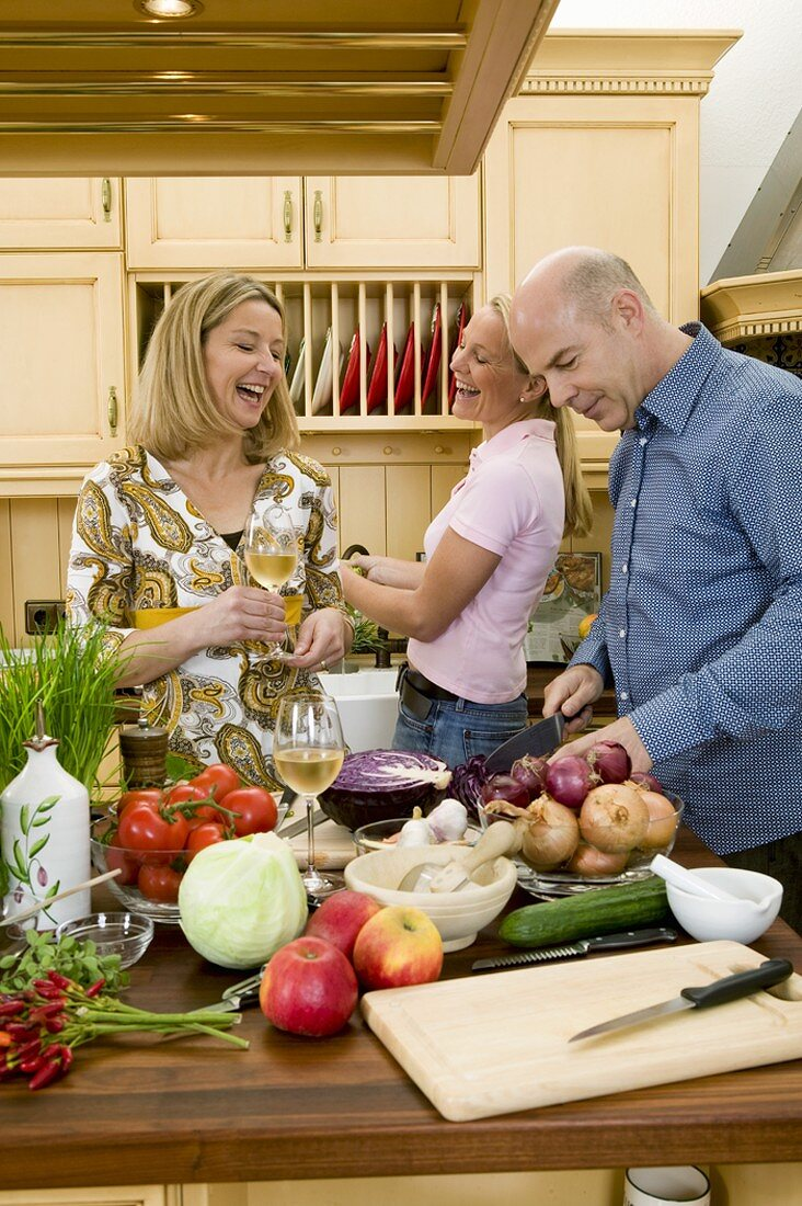 Two women and a man preparing food together