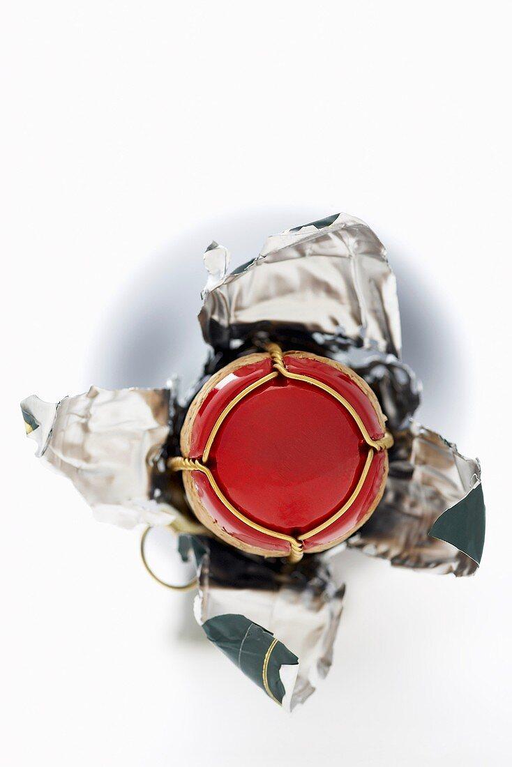 Verschluss einer Schaumweinflasche mit geöffneter Folie