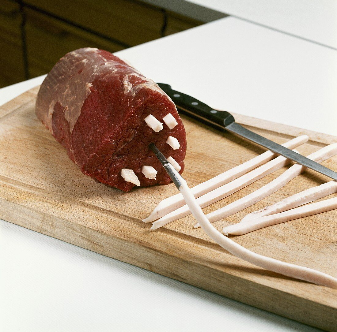 Larding a joint of beef with strips of pork fat