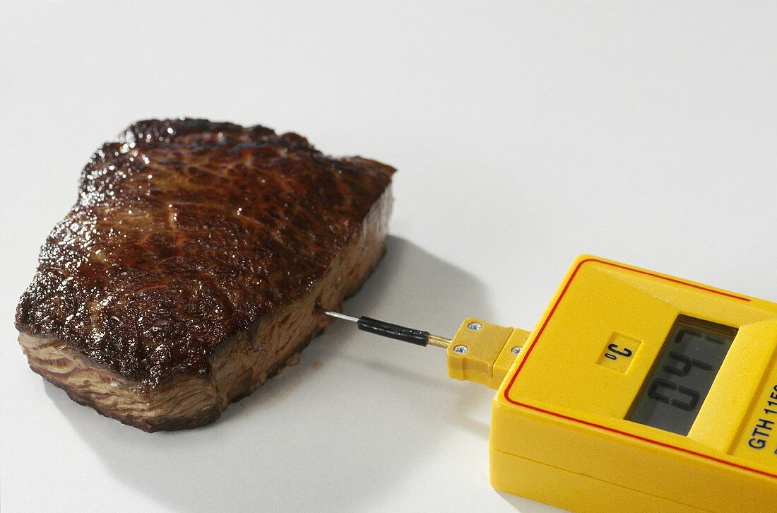 Checking beef steak to see if it is cooked