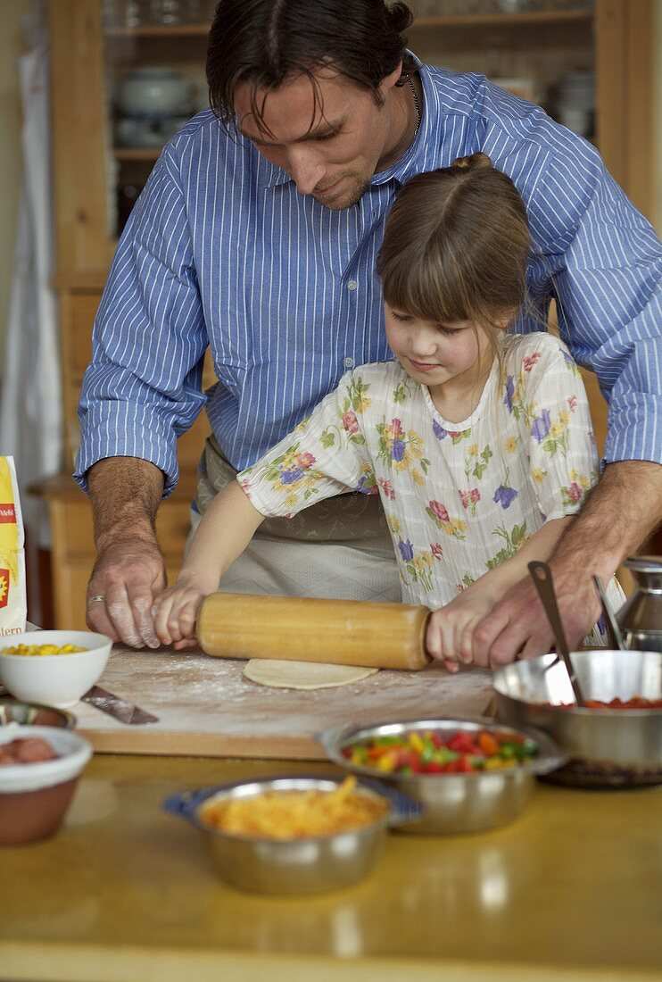 Father and daughter rolling out pizza dough together