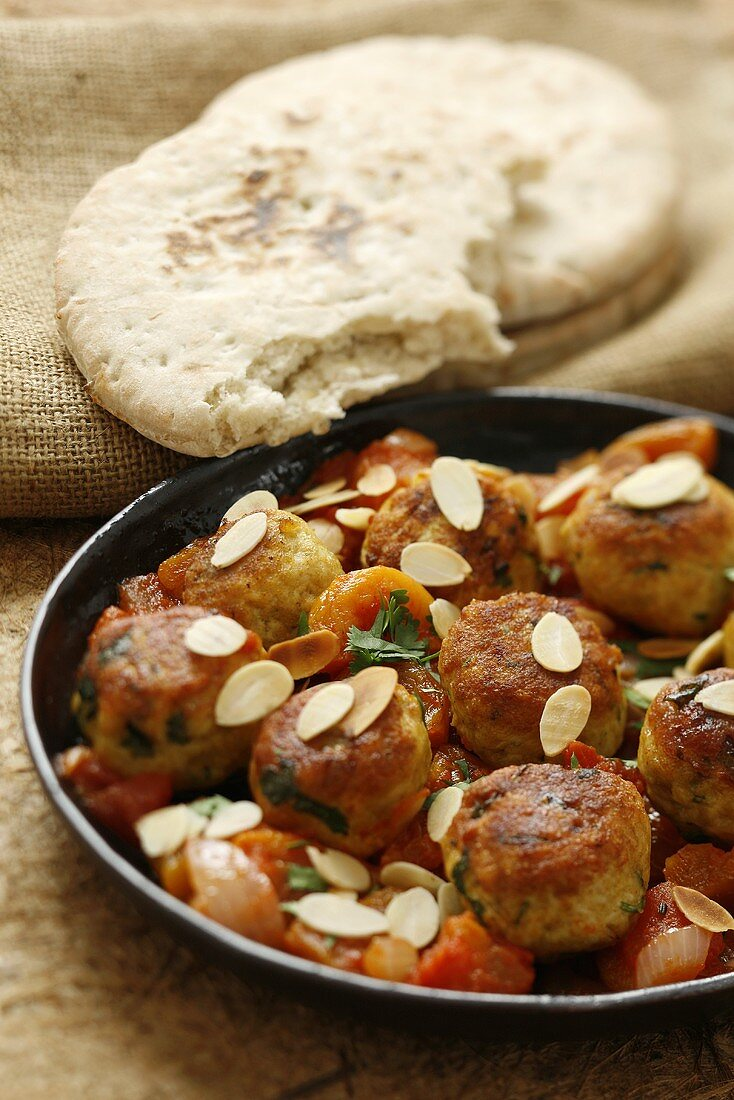 Meatballs with tomato sauce, apricots and flaked almonds