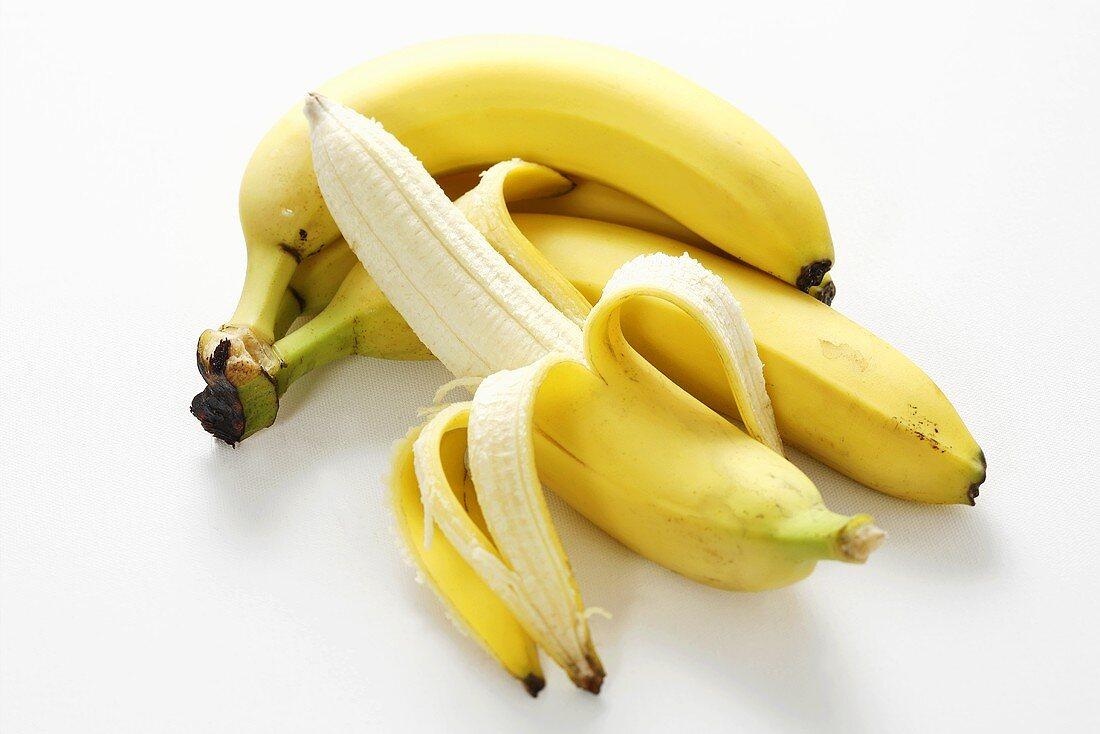 Half-peeled banana in front of small bunch of bananas