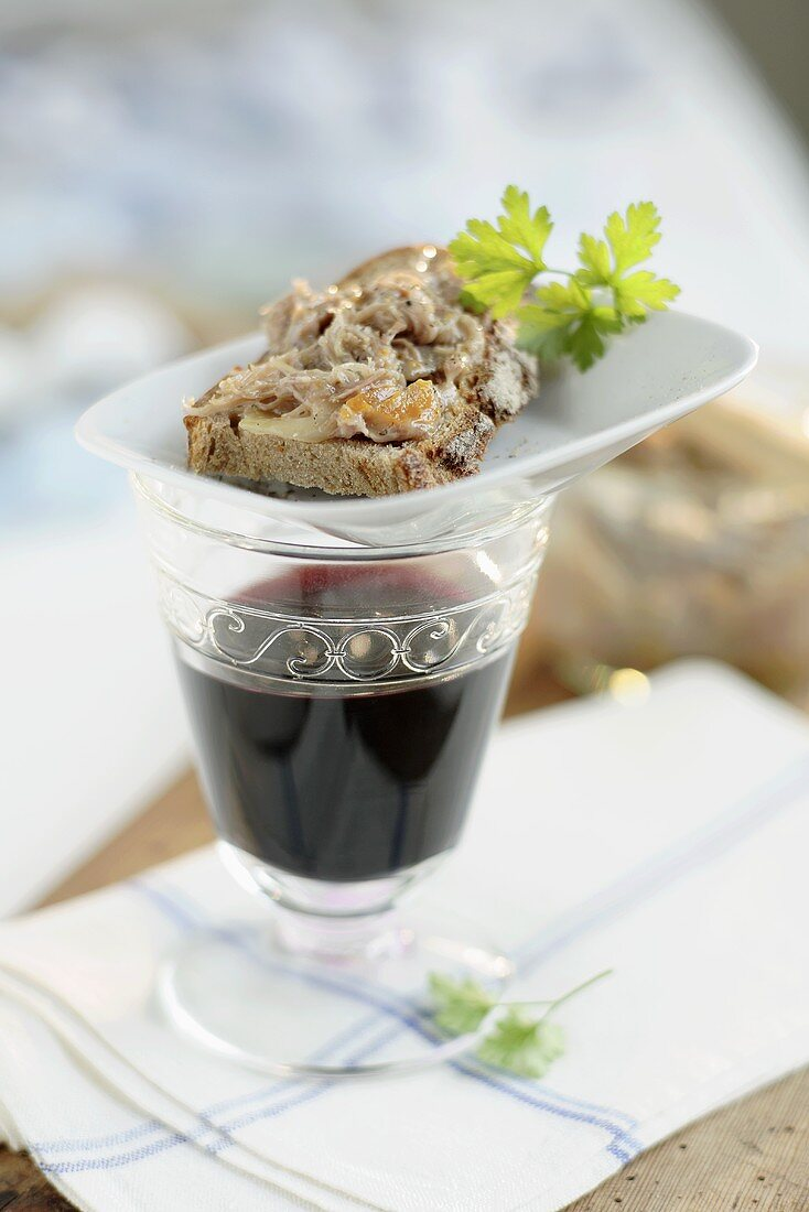 Goose rillettes on a slice of bread, glass of red wine