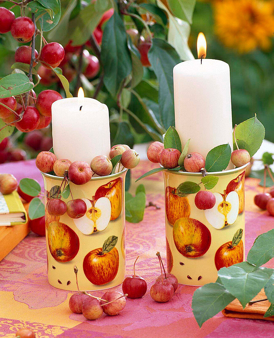 Candles in mugs filled with crab-apples