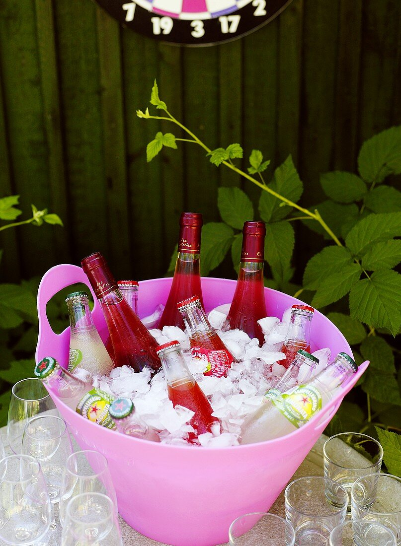 Rosé wine and various soft drinks in an ice bucket