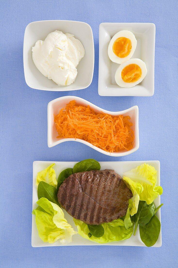 Low-calorie lunch: steak, carrots, yoghurt, egg