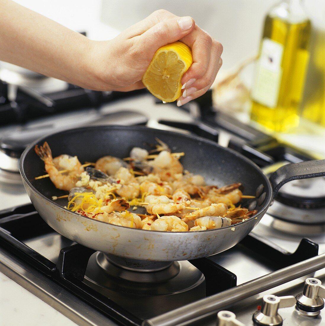 Sprinkling prawn skewers with lemon juice