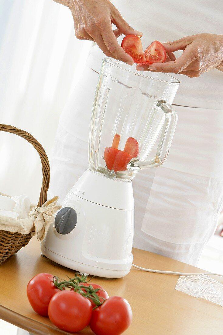 Putting tomatoes into a liquidiser (for tomato mask)