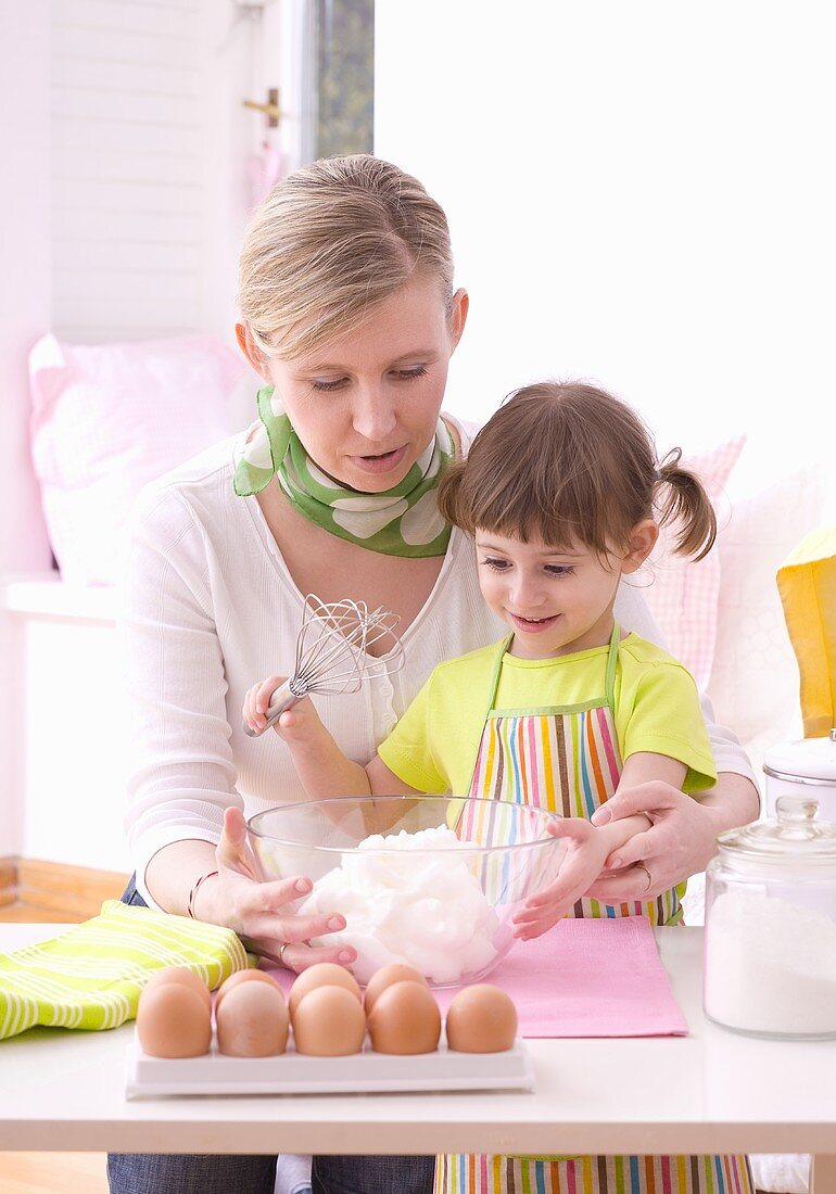 Mother and daughter holding a bowl of beaten egg white