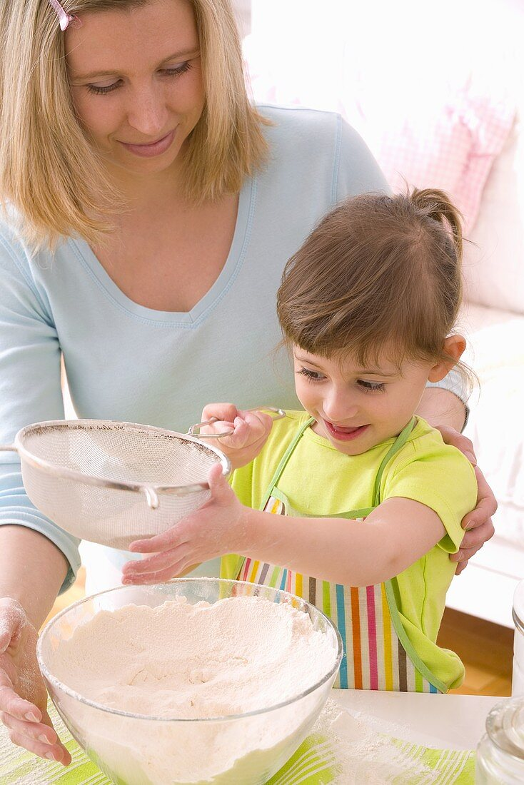 Mother and daughter sieving flour into a bowl