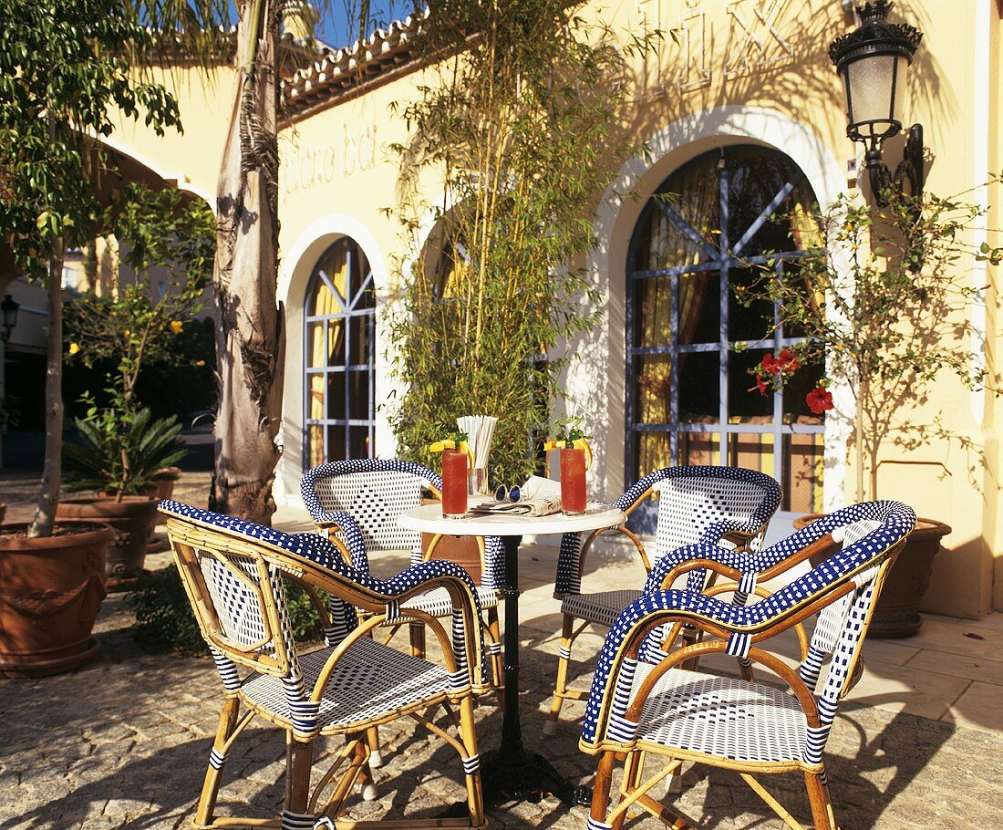 Small table with drinks, rattan chairs out of doors