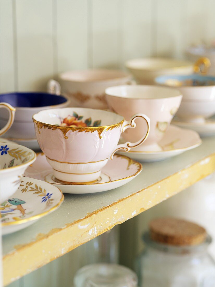 Old china cups and saucers on a shelf